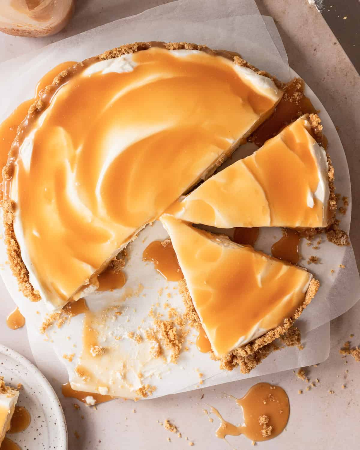 overhead shot of the cheesecake cut into slices with the caramel sauce dripping down the sides.