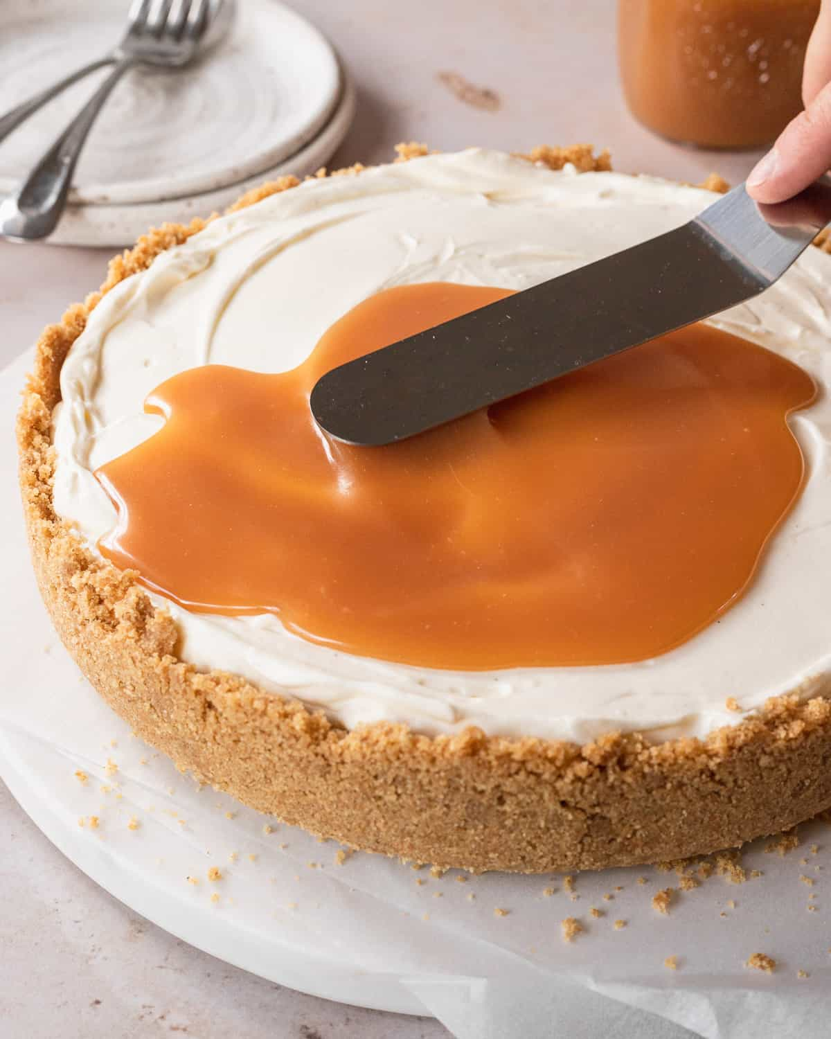 spreading the caramel sauce over top the cheesecake using an offset spatula
