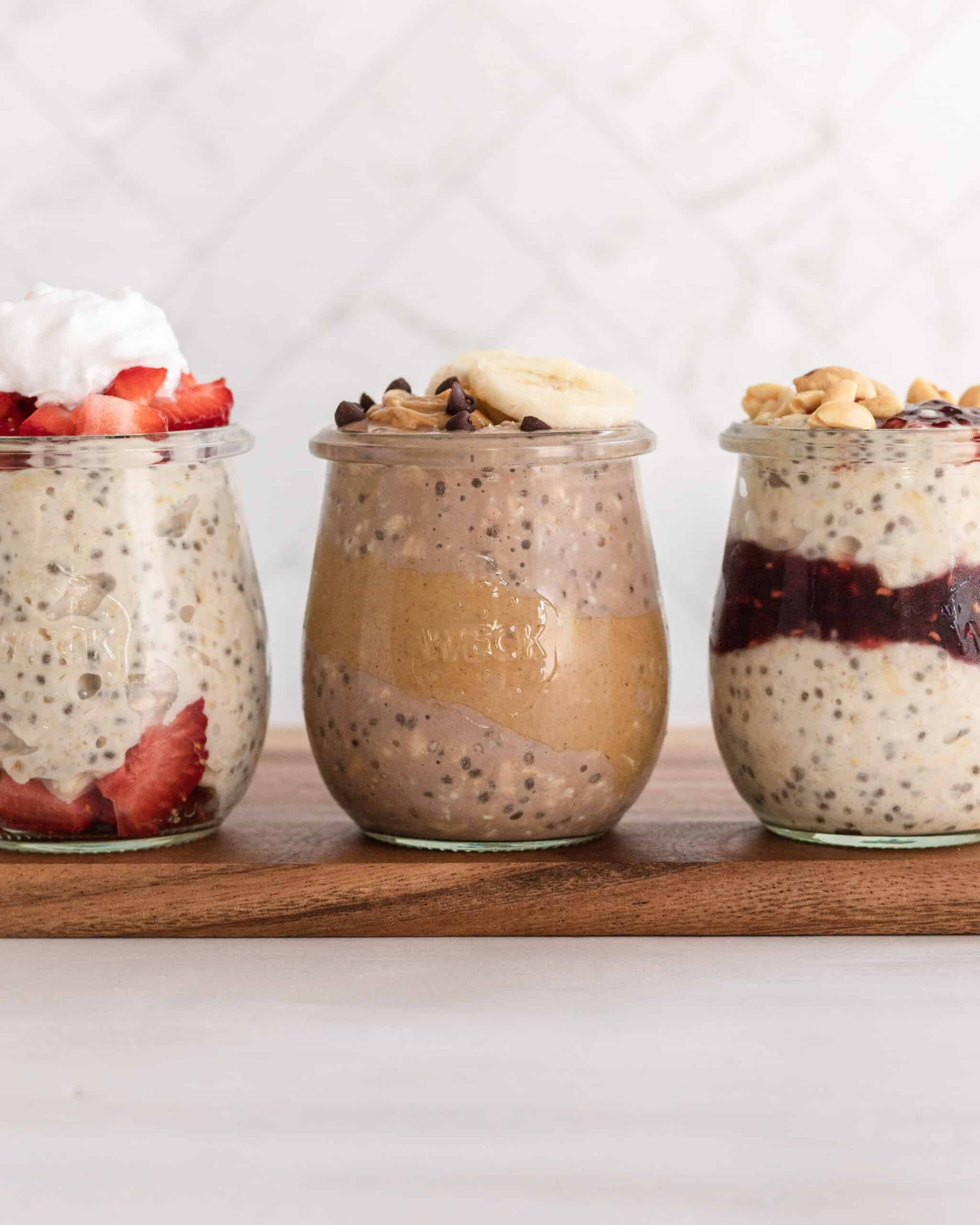 3 high-protein overnight oats variations in clear jars on a wooden board.