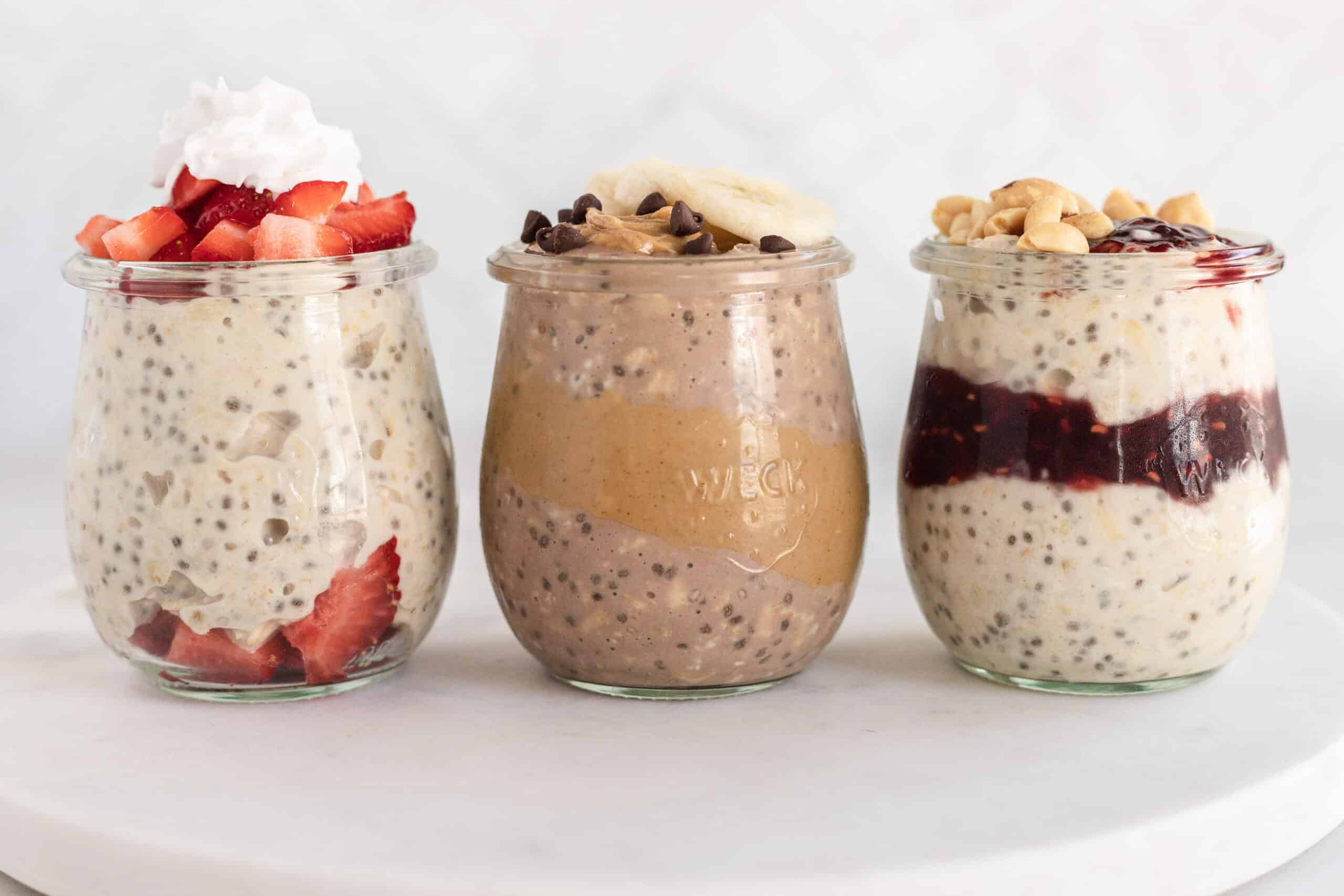 3 clear jars of different overnight oats on a white marble platter