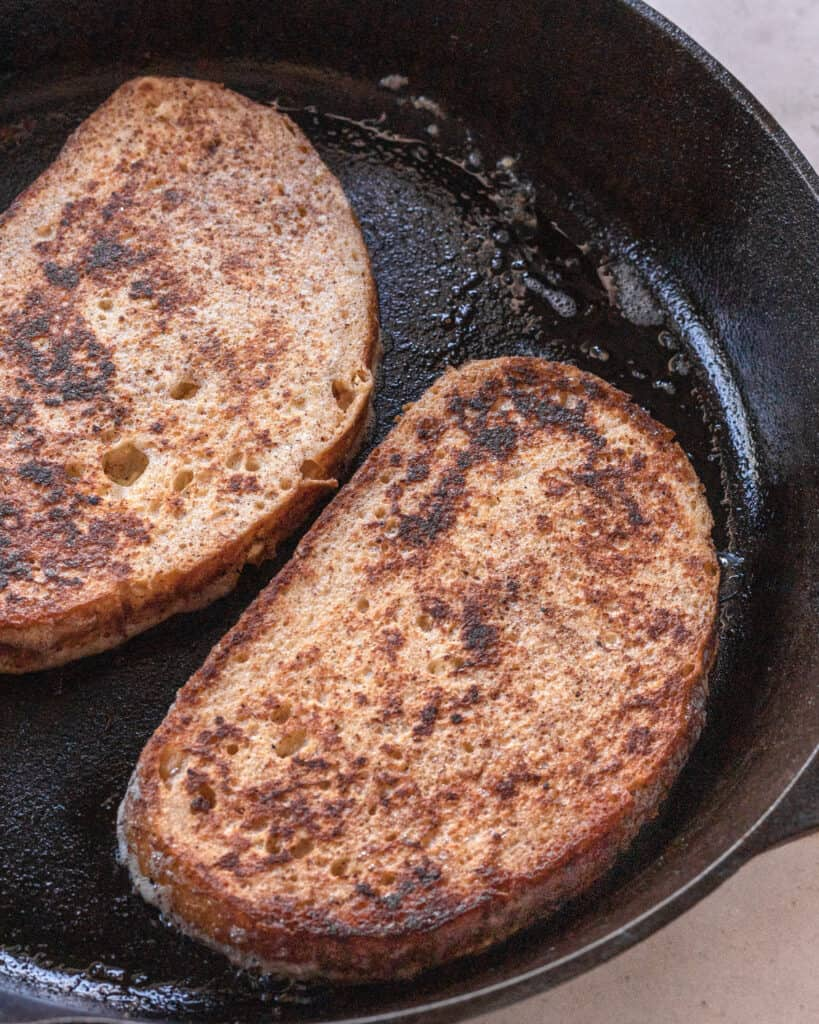two slices of brea in a cast iron skillet after being flipped and are golden brown on one side.