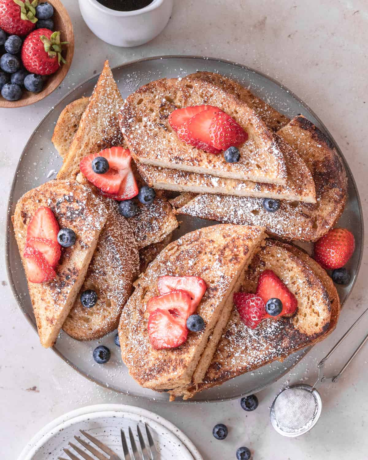 overhead shot of french toast slices on a round serving platter with berries and powdered sugar on top.