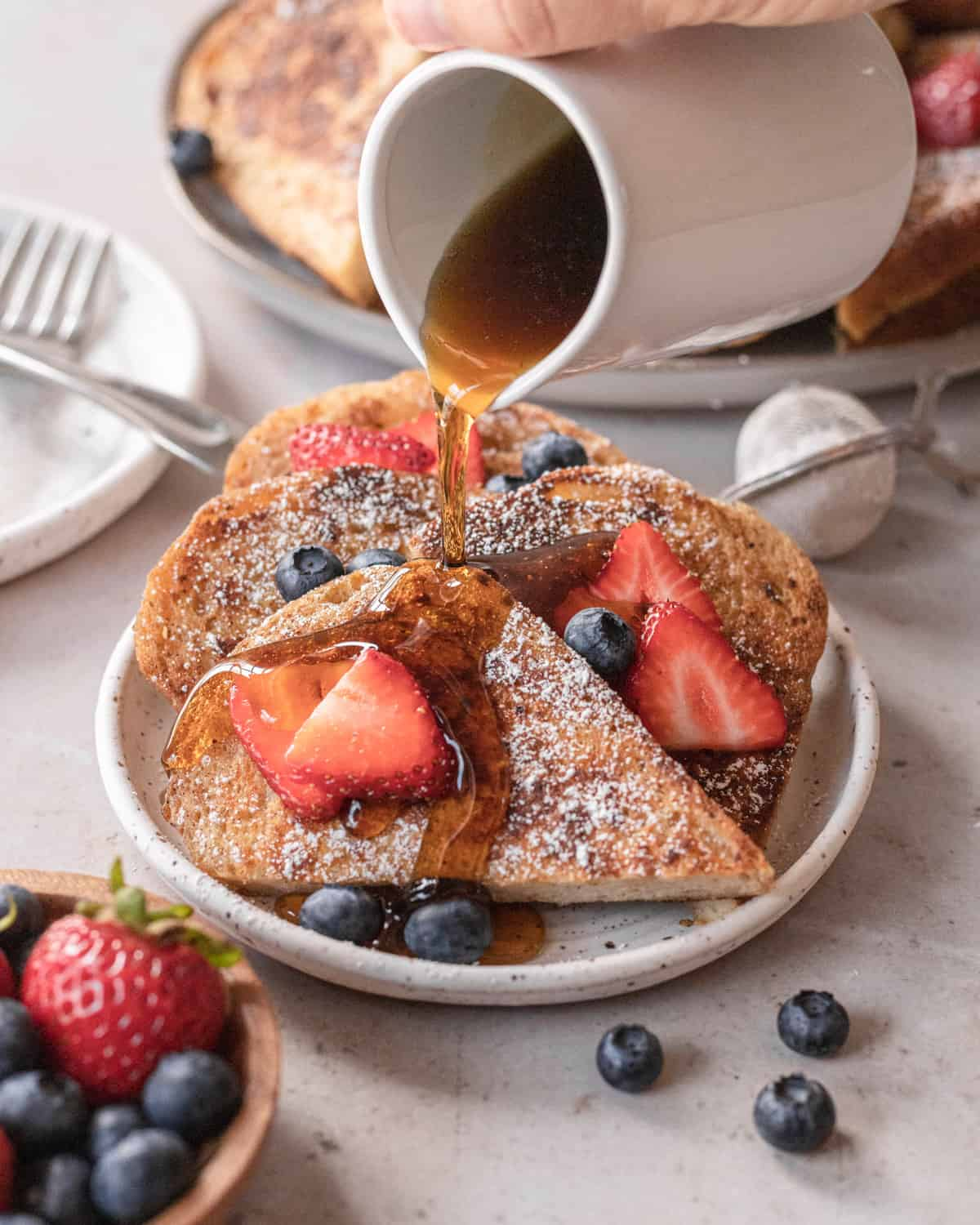 sliced french toast on a plate with maple syrup being poured over top surround by berries.