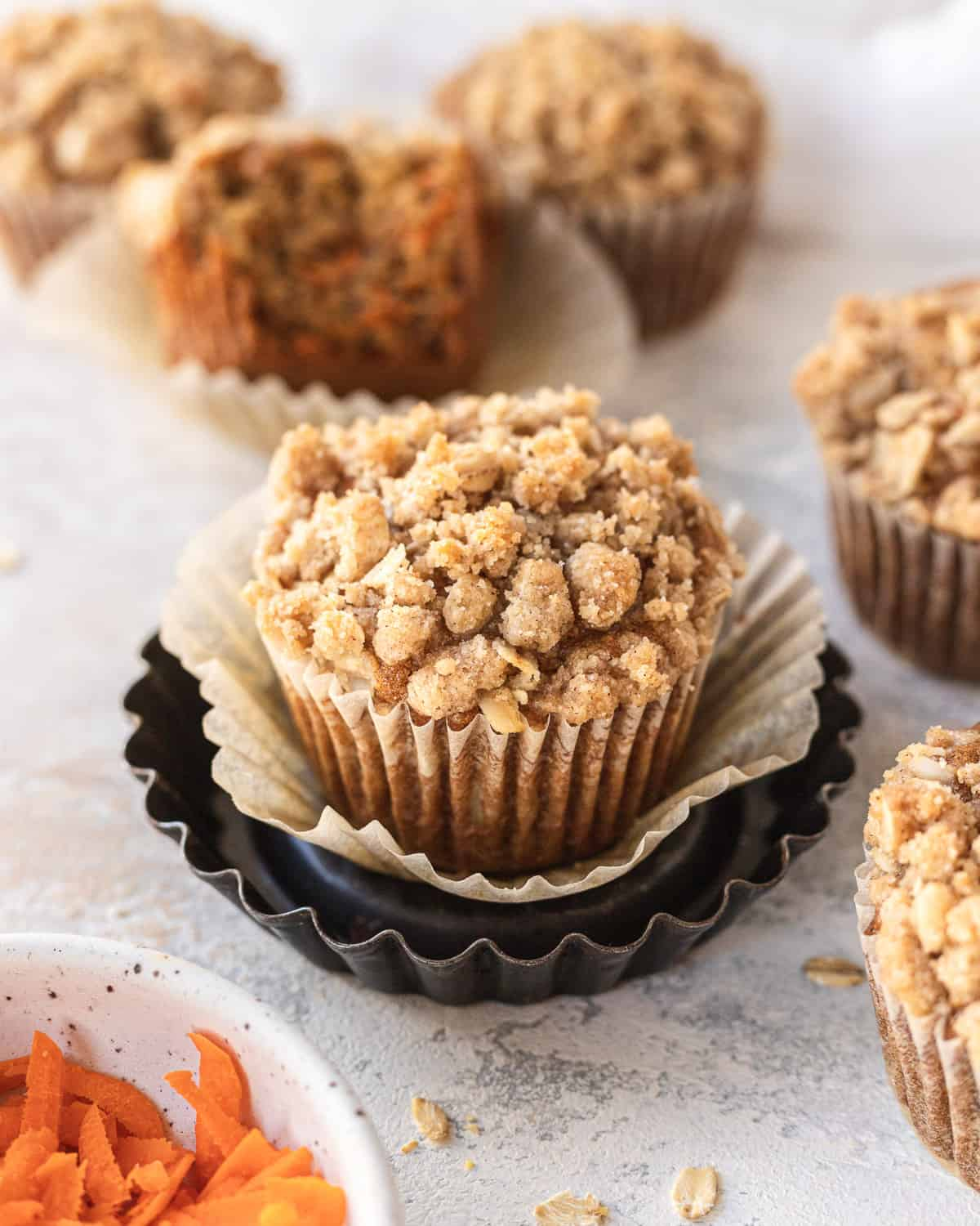 banana carrot muffin sitting in a little dish with muffins and a bowl of carrots surrounding it