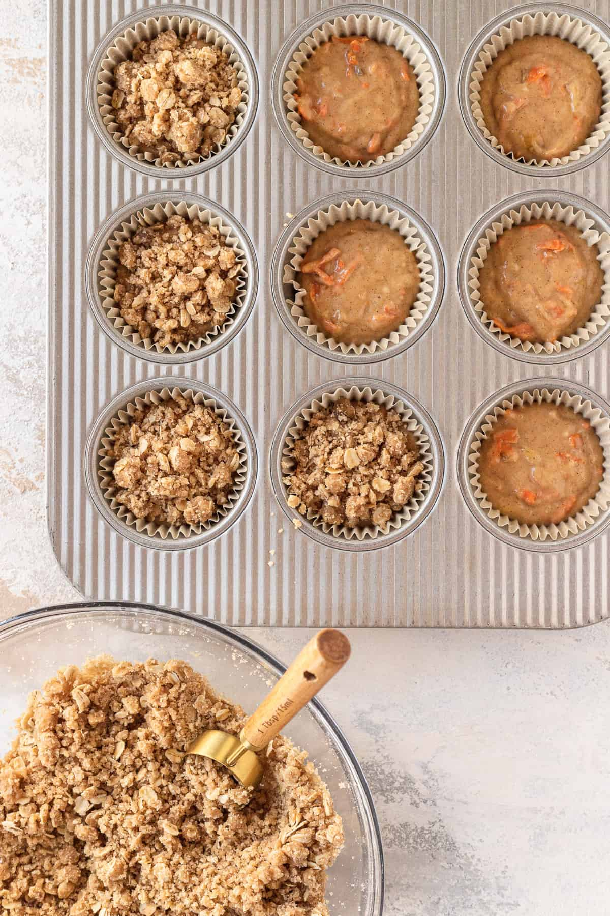 muffin batter in muffin pan with oat streusel being scooped on top
