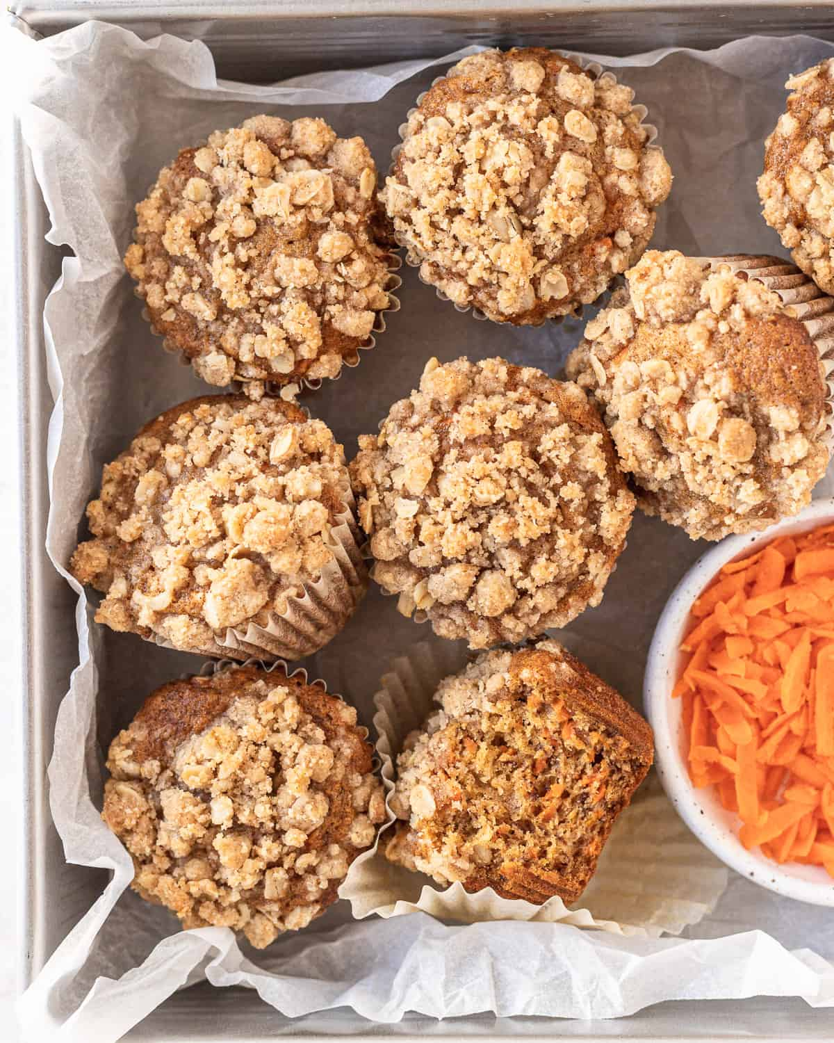 banana carrot muffins in a parchment-paper lined dish with a bowl of grated carrots