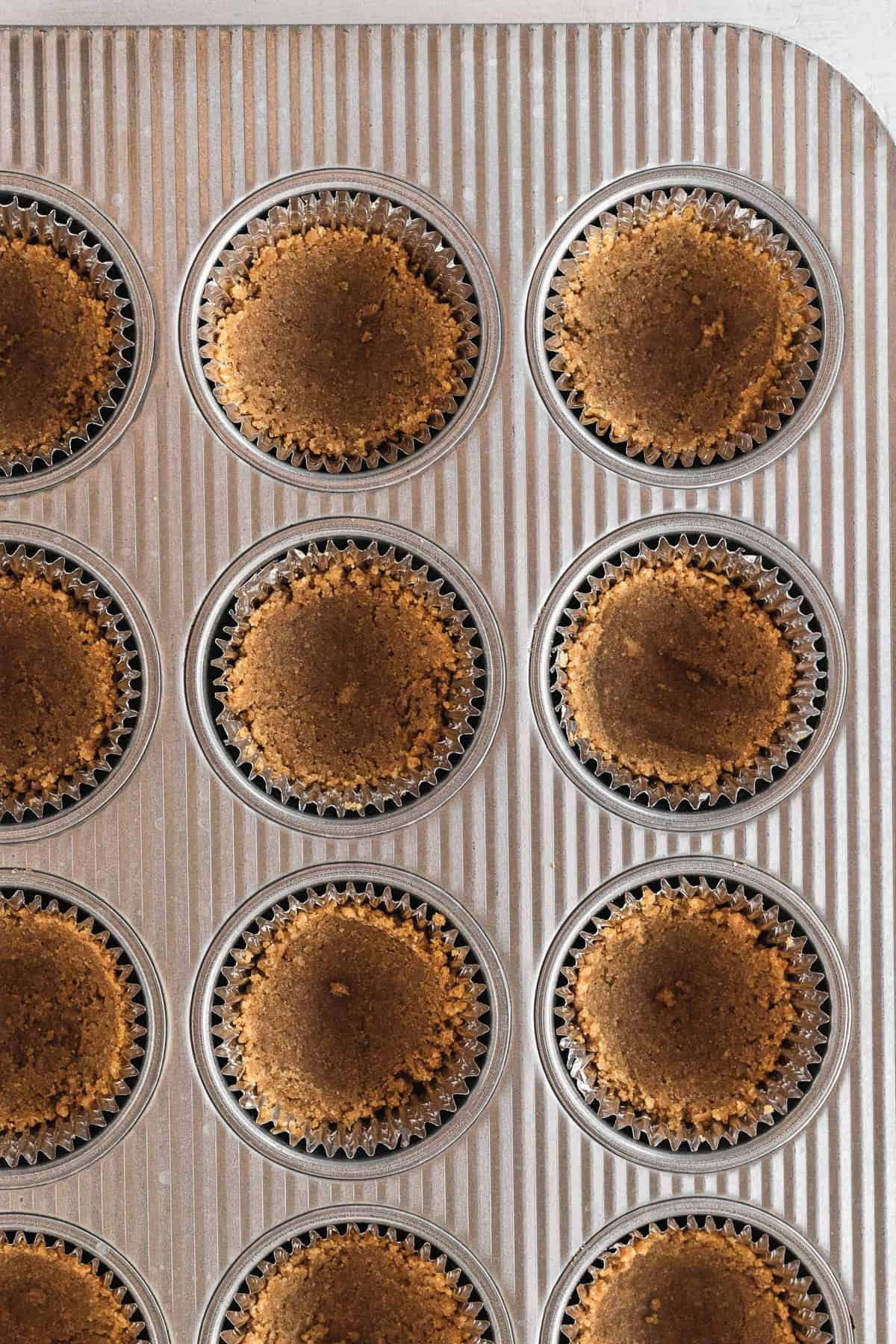 graham cracker crusts in the muffin tin after baking